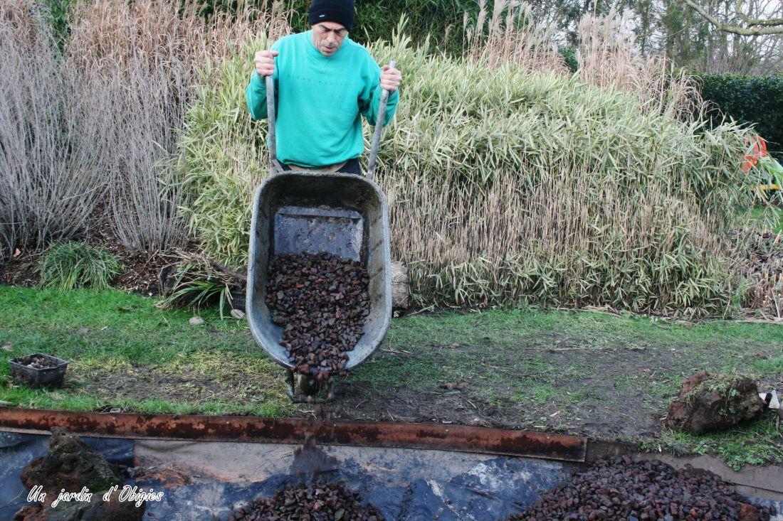 Dépose de pierres de lave dans le bassin de lagunage, un jardin d' Obigies